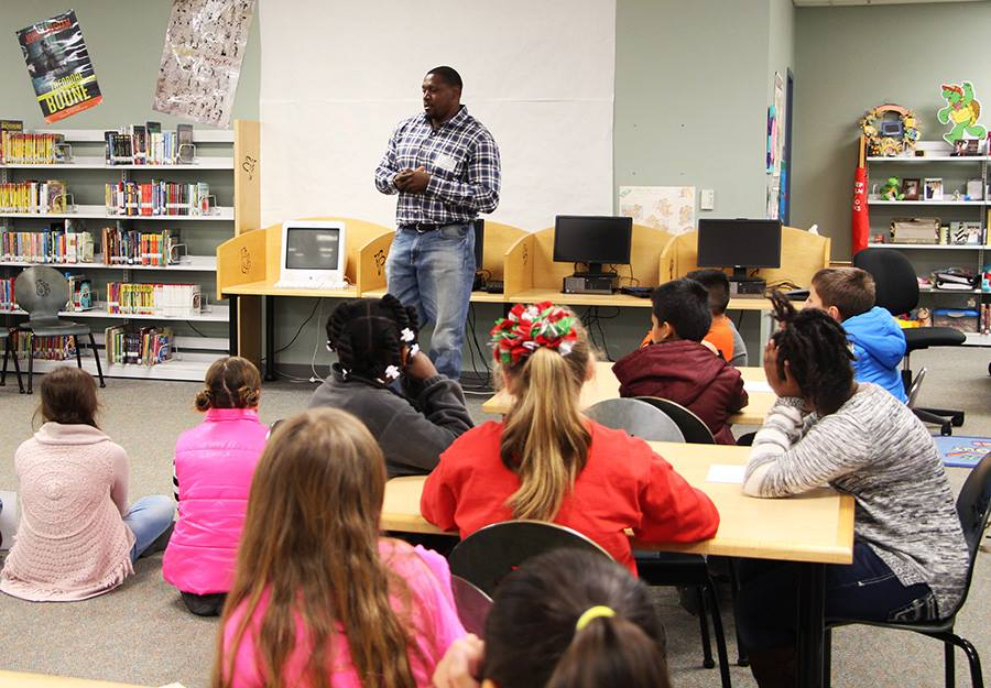 Man speaking to children in a library